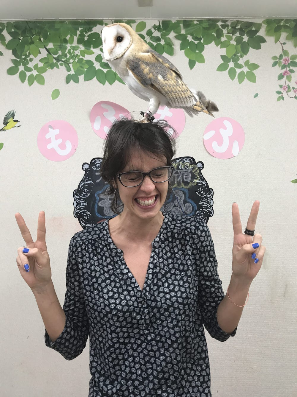 Woman poses with an owl on her head