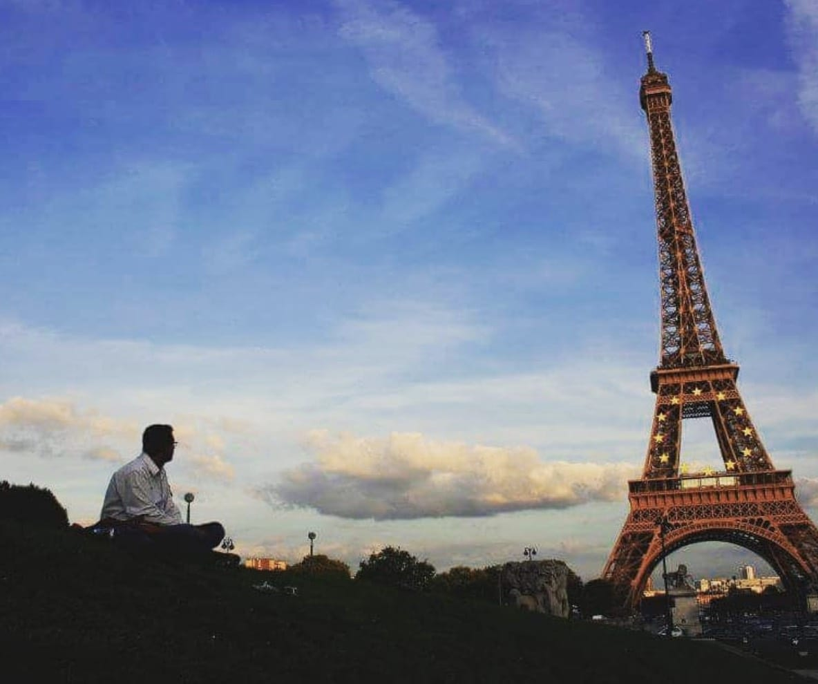 Man sits near the Eiffel Tower