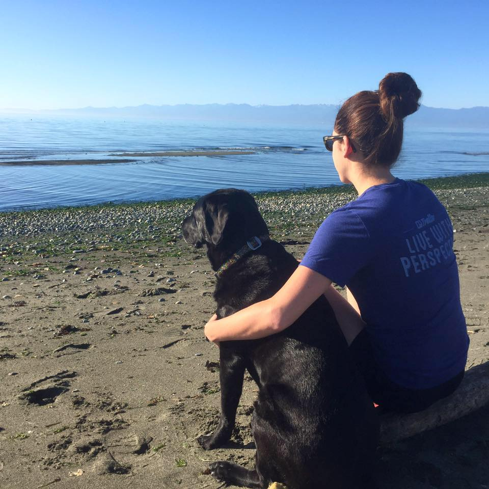 Woman sits on a beach with a dog
