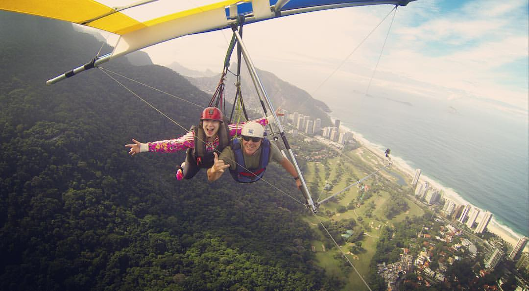 People wave from a hang glider